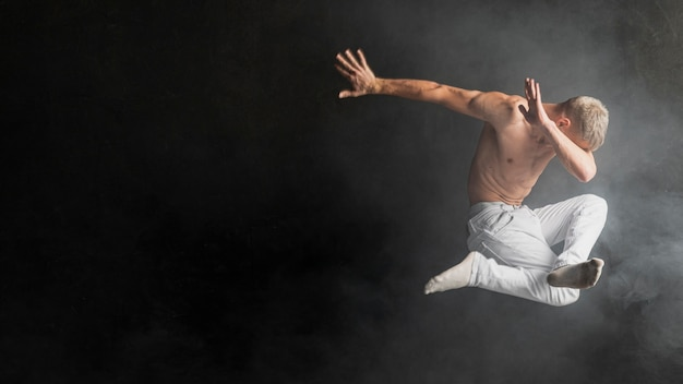 靴下とジーンズで空中でポーズをとる男性パフォーマーの側