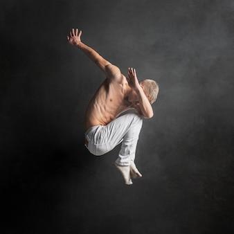 Вид сбоку танцор позирует в воздухе