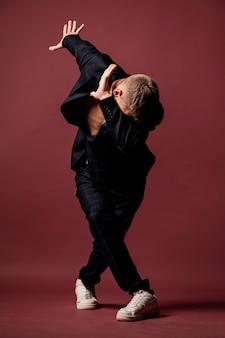 男性のパフォーマーのスーツとスニーカーのダンスの正面図