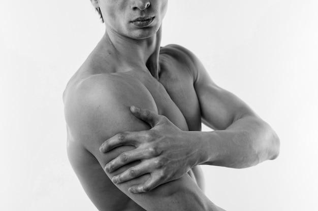 Вид сбоку спортивного человека позирует без рубашки в черно-белом