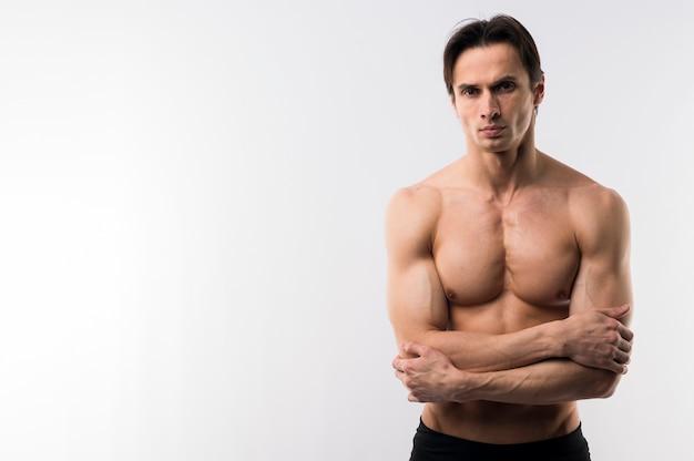 コピースペースで上半身裸のポーズ運動男の正面図