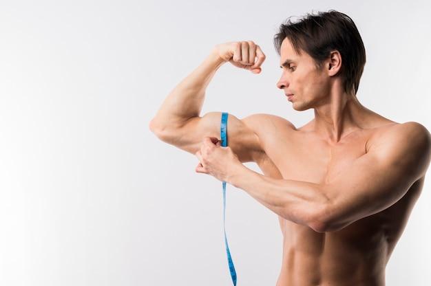 Вид спереди спортивного человека, измеряющего бицепс