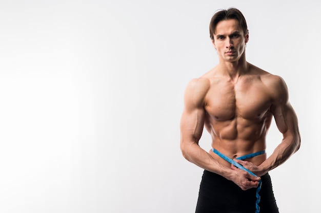 測定テープで上半身裸の運動男の正面図