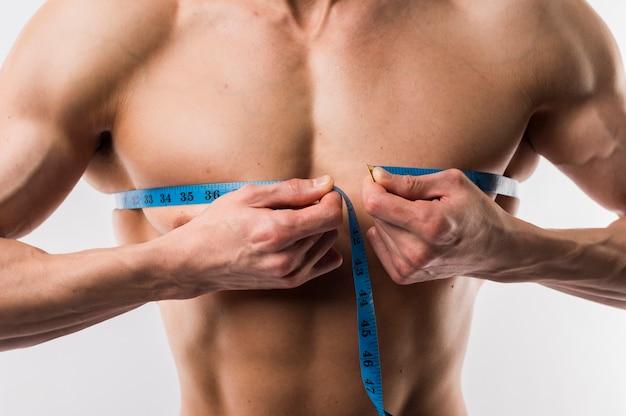 筋肉の胸を測定する男のクローズアップ