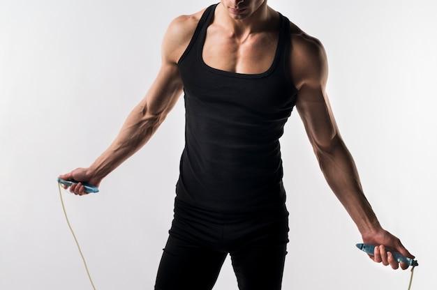 Средний снимок спортивного человека со скакалкой
