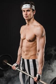 重みを保持している筋肉質の男の側面図