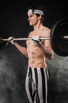 重りを持ち上げる上半身裸の男の側面図
