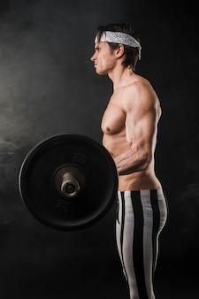 重りを持ち上げる筋肉質の男の側面図
