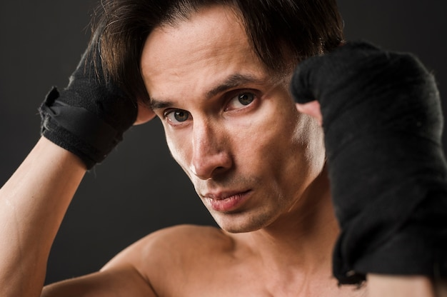 Атлетик мужчина позирует в боксерских перчатках