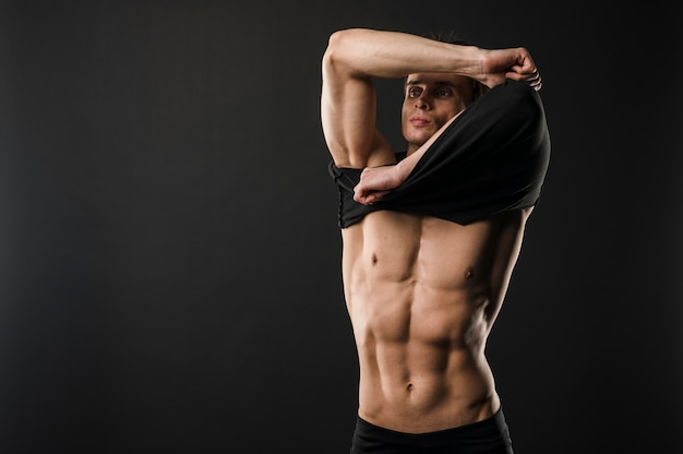 Мускулистый спортивный человек снимает футболку с копией пространства