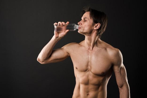Без рубашки спортивный мужчина пьет из бутылки с водой