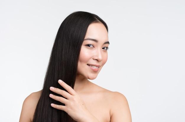 Улыбающаяся женщина ухаживает за волосами