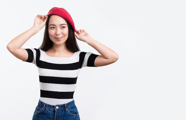 若い女性が彼女の帽子を修正