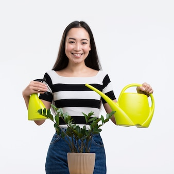 Вид спереди женщина поливает цветок