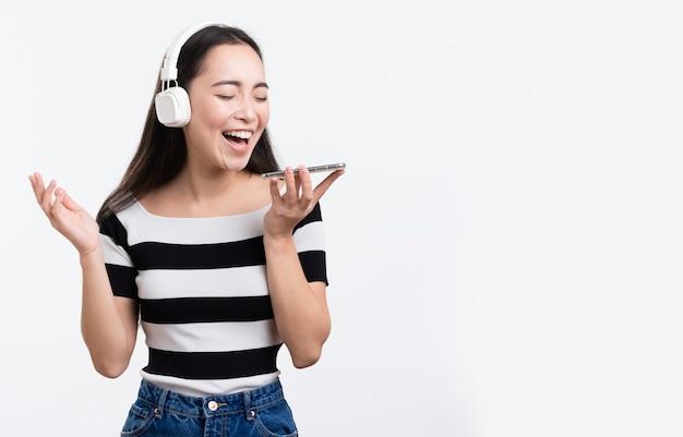 Молодая женщина прослушивания музыки на мобильном телефоне