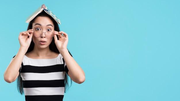 Игривая женщина с книгой на голове