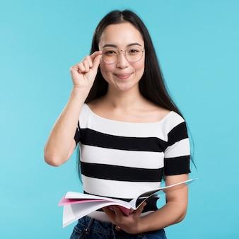 Молодая женщина в очках держит книгу