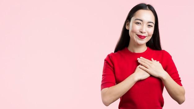 Копия пространство женщина с красными губами с рукой на сердце
