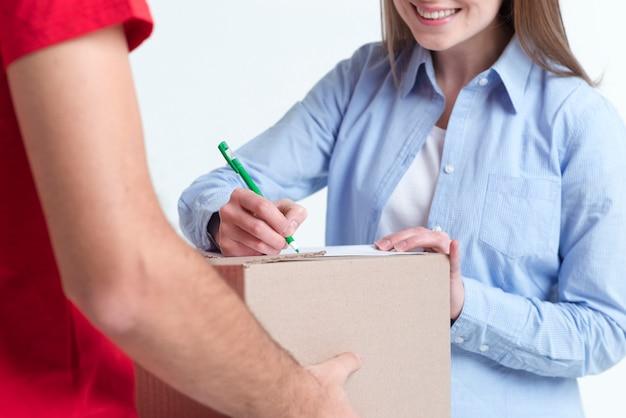Довольный клиент онлайн доставки подписывает формы крупным планом