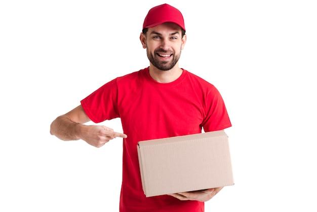 Изображение молодой доставщик, указывая на коробку