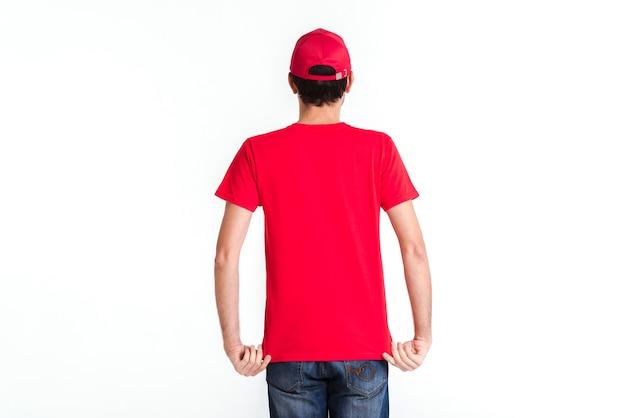 Стоящий курьер человек в красной форме от вид сзади