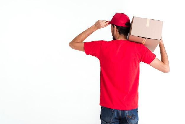 Стоящий курьер мужчина держит коробку и кепку с заднего выстрела