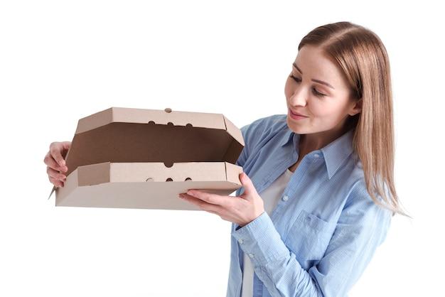 Средний снимок женщины, заглядывающей в коробку с пиццей