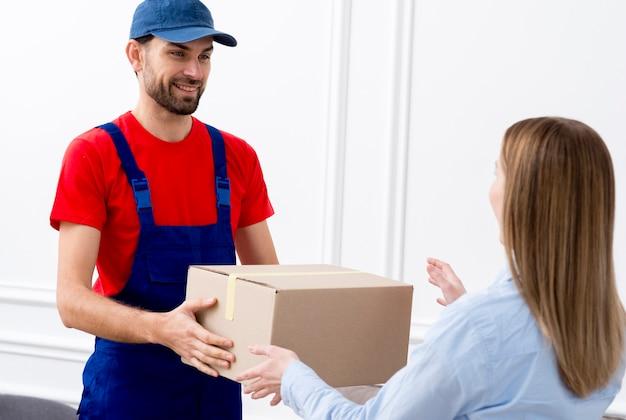 Курьер мужчина доставляет картонную коробку женщине