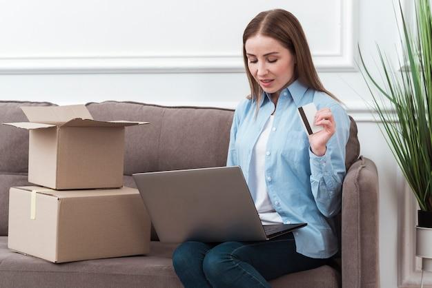 Женщина смотрит на свой ноутбук и держит кредитную карту