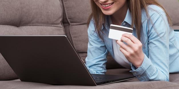 Женщина держит ноутбук и вид спереди кредитной карты