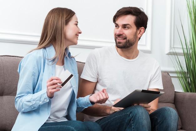 かわいいカップルがお互いを見て、オンライン購入のためのデジタルデバイスを保持