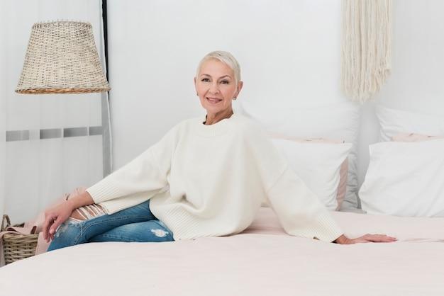 幸せな高齢女性がベッドでポーズ