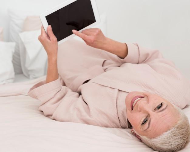 Высокий угол пожилой женщины позирует и улыбаясь, держа планшет