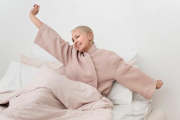 Пожилая женщина в халате растягивается в постели