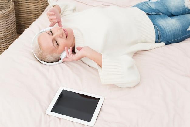 Счастливая пожилая женщина наслаждаясь слушать музыку с наушниками в постели