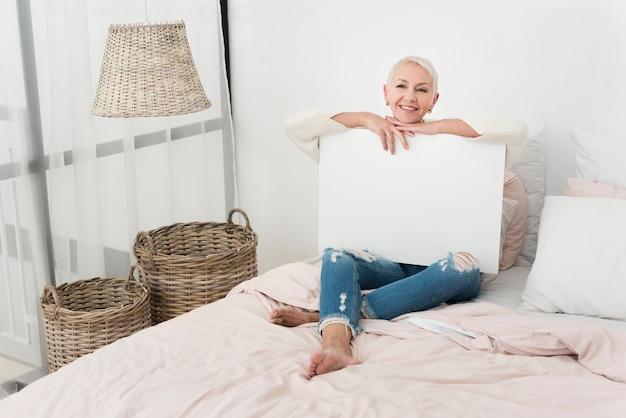 ベッドで空白のプラカードを保持しているスマイリー高齢女性