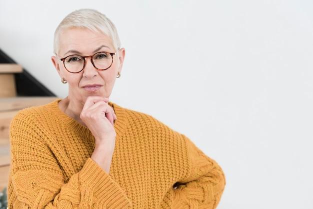 コピースペースで物思いにふける長老女性の正面図