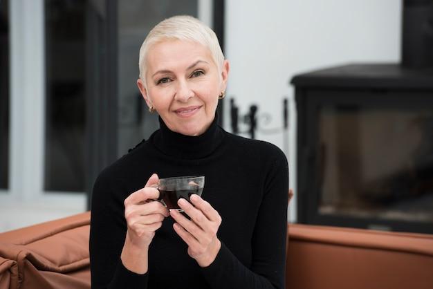 Вид спереди счастливой зрелой женщины позируют с чашкой кофе