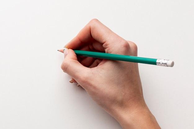 鉛筆を持っているクローズアップ手