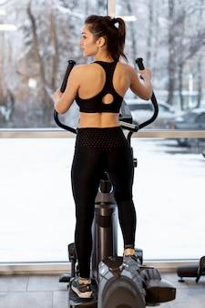Женщина тренируется на велосипеде