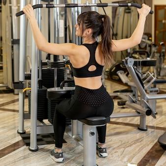 Женщина высокого угла разрабатывая в спортзале