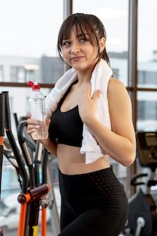 Высокий угол молодая женщина в тренажерном зале