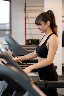 Женщина высокого угла в спортзале на беговой дорожке