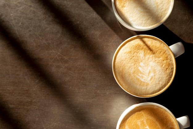 Вид сверху вкусные кофейные чашки с молоком на столе