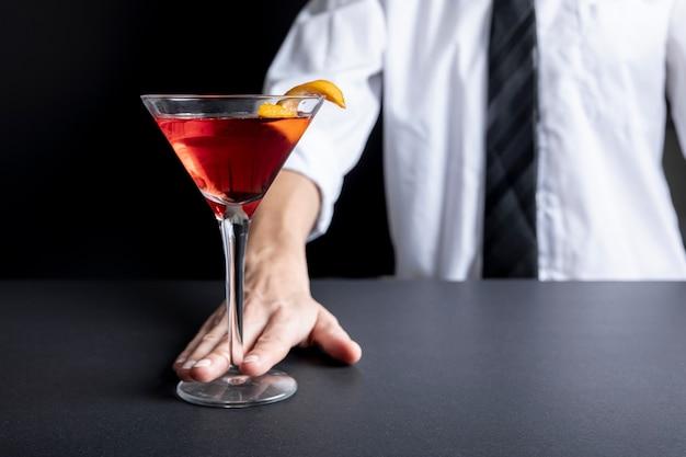 新鮮なアルコールカクテルを提供するクローズアップバリスタ