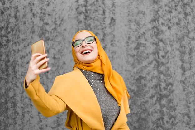 Привлекательная молодая мусульманская женщина, принимая селфи