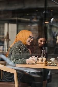Счастливая молодая девушка смеется с друзьями