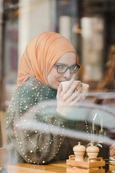 Портрет молодой девушки, наслаждаясь кофе