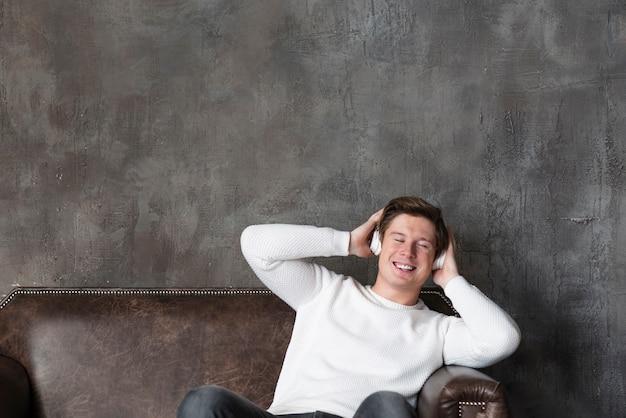 Современный человек слушает музыку в наушниках, сидя на диване