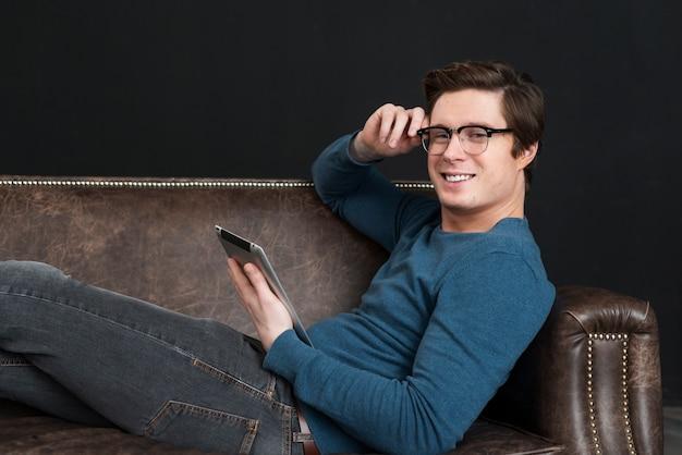 彼のソファに滞在しながら彼のタブレットを保持している男